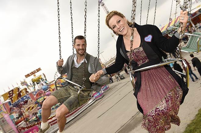 Martin Tomszyk mit Ehefrau Christina Surer fahren Kettenkarussell. Das Dirndl hält!
