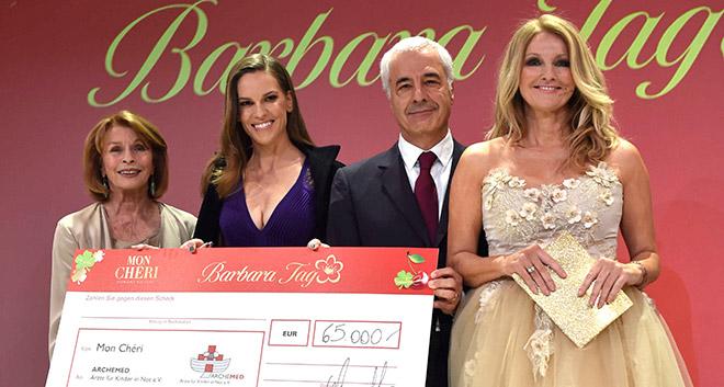 Gemeinsam mit Carlo Vassallo, dem Geschäftsführer von Ferrero Deutschland, übergab Hilary Swank auf der Bühne den Barbara Tag Spendenscheck in Höhe von 65.000 Euro an 'Archemed - Ärzte für Kinder in Not e.V.'. Fotocredit: BrauerPhotos