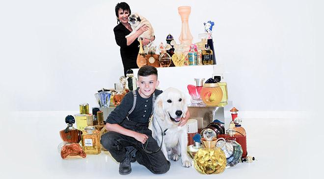 Ben Neumann mit seinem VITA-Assistenzhund Quest inmitten einer Auswahl der zu versteigernden Parfum-Flakons. Dahinter Uschi Ackermann mit Mops Sir Henry. Fotocredit: Terence Tremper
