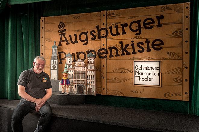 Klaus Marschall leitet das Theater in dritter Generation, das 1948 in das Heilig-Geist-Spital in Augsburg eingezogen ist. Seitdem gilt das Marionettentheater als populäres Wahrzeichen der Stadt und ist damit eine der Stadtverführungen der 'traditionell anders'-Geschichten von Bayern Tourismus.