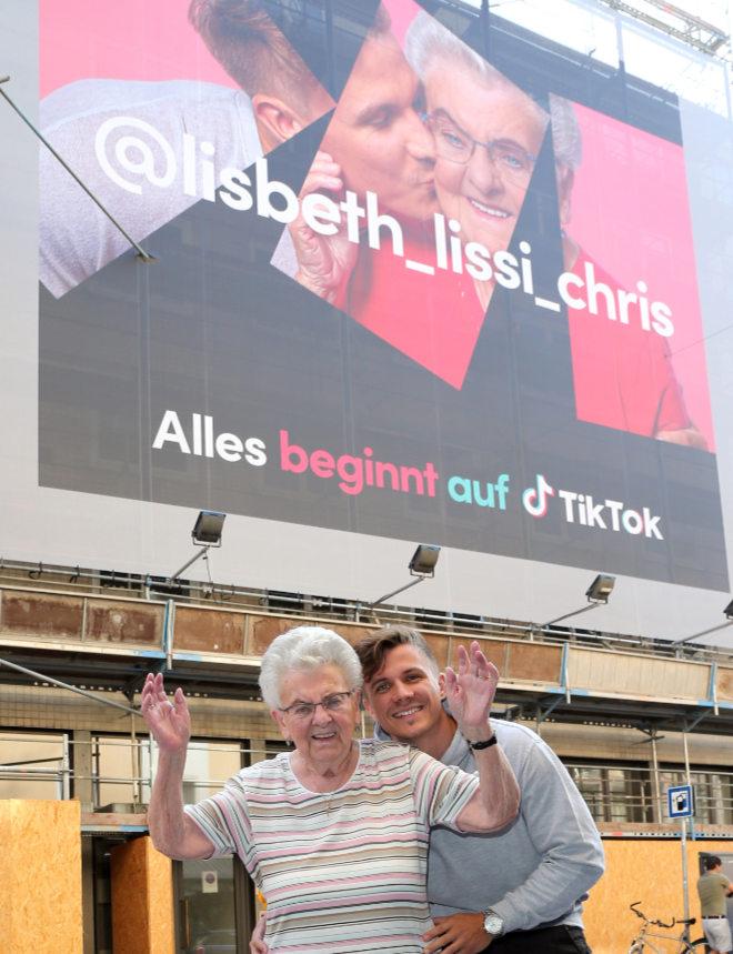 """Christian """"Chris"""" Kroemer zeigt seine Großmutter Elisabeth (Lissi auf TikTok) die brandneue Werbekampagne in der Landwehrstrasse. Dafür kamen die beiden aus ihrer Heimatstadt Nürnberg. Fotocredit: Gisela Schober/PR"""