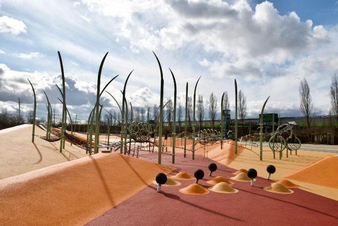 Im Hintergrund vom Wasserspielplatz kann man den Turm vom 39 Meter langen Fußgängersteg sehen, welcher alte und neue Stadtteile verbindet. Fotocredit: Schaller